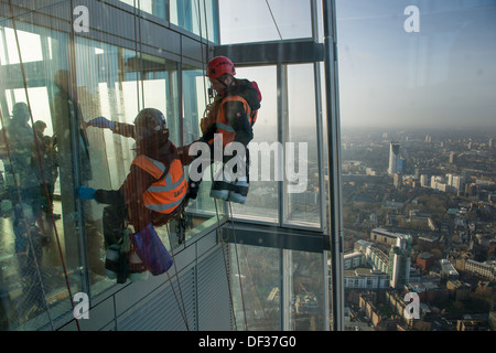 Abseiling window-cleaners cleaning the outside of the glass of the View from the Shard observatory, at the top of - Stock Photo