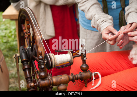 spinning wheel with hands making yarn from the wool - Stock Photo