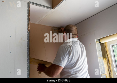 A plasterer working on a wall in a house. - Stock Photo