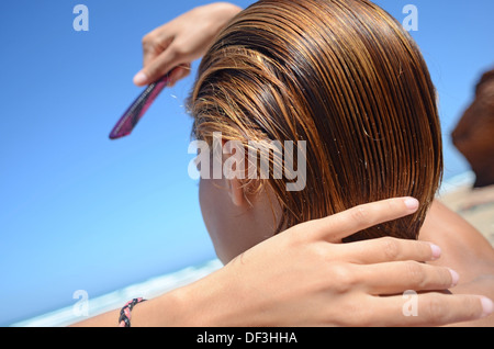 Young woman brushing her hair on the beach