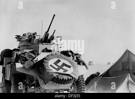 The image from the Nazi Propaganda! shows soldiers of the German Wehrmacht with a captured armored reconnaissance - Stock Photo