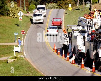 Worker stopping traffic for repairs by Power Crew - Stock Photo