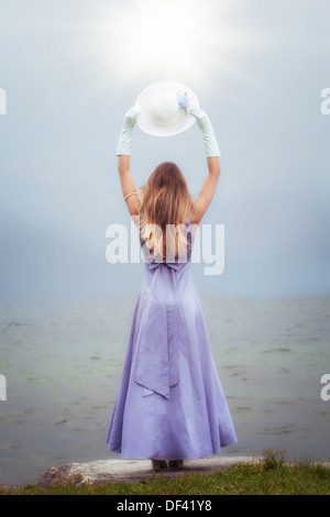 a woman in a purple dress is standing at a lake with a sun hat - Stock Photo