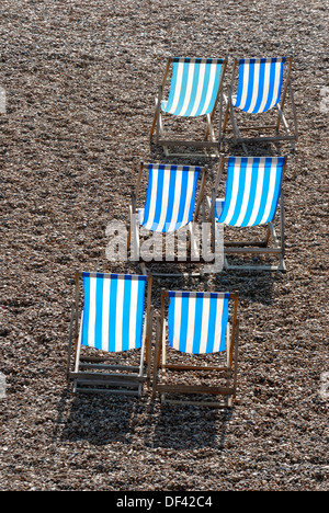 Brighton, East Sussex, England, UK. Deckchairs on the pebble beach - Stock Photo
