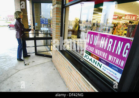 Now Hiring sign in a store window - Stock Photo