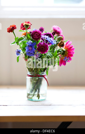 A small bunch of freshly picked flowers arranged in a small glass jar - Stock Photo