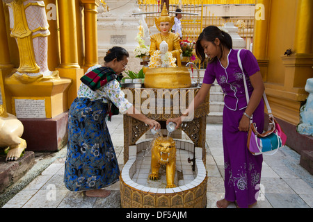 Women pour water over buddha statues at Shwedagon Paya in north central Yangon, Burma. - Stock Photo