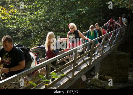 ngleton UK. 28th September, 2103. Members of Batala Samba Band crossing wooden footbridge en-route to Ingleton Falls - Stock Photo