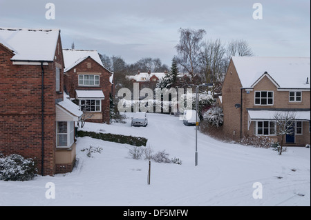 High view over residential area with modern detached houses in a quiet, snow-covered cul-de-sac on cold winter day - Stock Photo