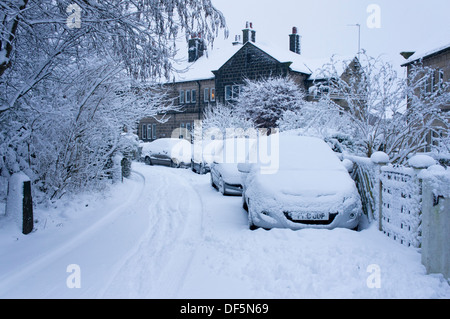 Winter scene with cars parked outside semi-detached houses on quiet residential street, all covered in blanket of - Stock Photo