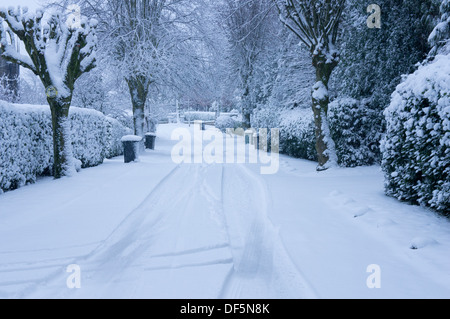 Winter wonderland scene - quiet tree-lined, residential street with road & pavements, covered in blanket of white, - Stock Photo