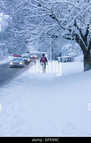 Winter scene with snowy driving conditions for cars on road & lone pedestrian walking on snow-covered pavement  - Stock Photo
