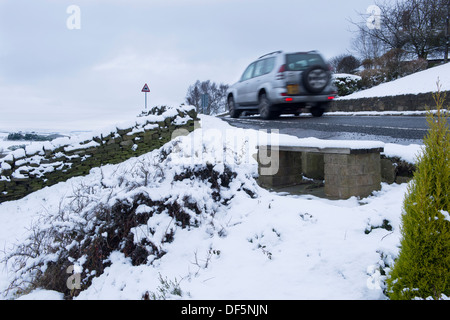 Blurred motion of Toyota Land Cruiser 4x4, traveling past white fields along country lane on a cold, snowy winter's - Stock Photo