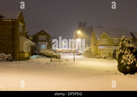 Starburst light from steet lamps at nighttime illuminate private modern houses in cold, snow covered cul-de-sac - Stock Photo