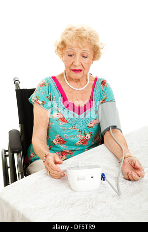 Senior woman taking her own blood pressure at home, worried about the results. Isolated on white.  - Stock Photo