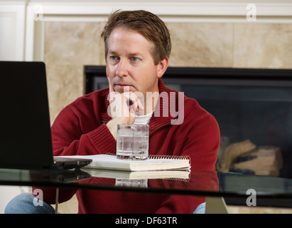 Photo of mature man, dressed casually while sitting down at glass table, working from home, looking at computer - Stock Photo