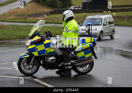 A Motorcycle Police Traffic Officer directing traffic at a road block - Stock Photo