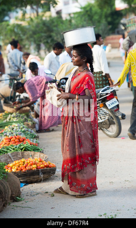 Poor lower caste Indian woman at a street market carrying a pot of rice on her head collecting the unsellable food. - Stock Photo