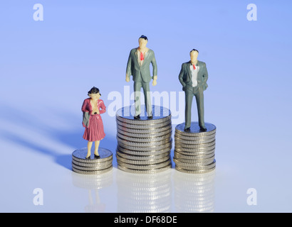 Mini plastic men and a woman standing on piles of money - Stock Photo