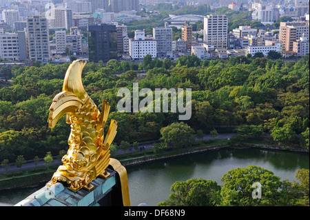 View from the top floor of Osaka castle with the park and business city sector and a golden fish. - Stock Photo