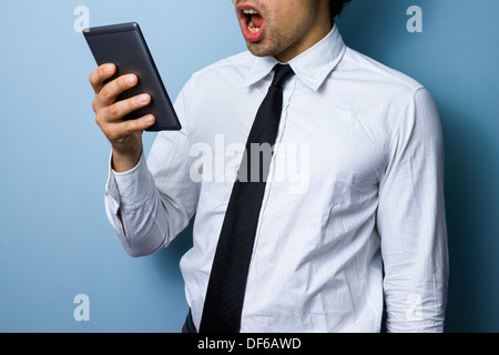 Young businessman is surprised by what he is reading on his digital tablet - Stock Photo