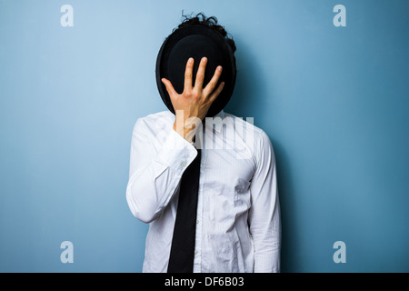 Young man hiding his face behind his bowler hat - Stock Photo