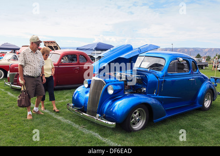 Spectators at a Classic Car show near Grand Junction, Colorado looking at a customised and street racing automobile. - Stock Photo
