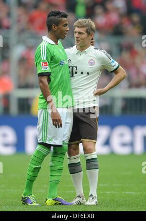 Munich's Toni Kroos (R) vies for the ball with Wolfsburg's Luiz Gustavo during the football match between FC Bayern - Stock Photo