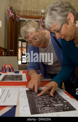 Two elderly women browsing old photographs at a village history open day, Buriton, Hampshire, UK. - Stock Photo