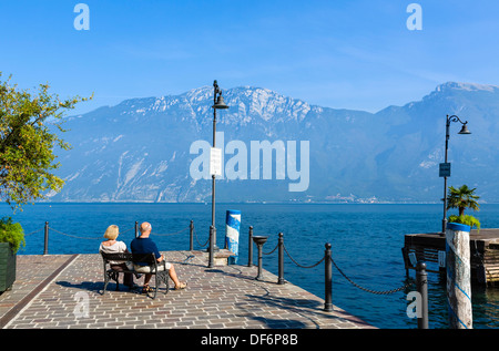 Middle aged couple sitting on the lakefront in Limone sul Garda, Lake Garda, Italian Lakes, Lombardy, Italy - Stock Photo
