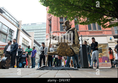 A levitating street artist performs on Market Street in Manchester city centre, watched by passers by. - Stock Photo