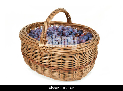 ripe plums in basket isolated on white background - Stock Photo