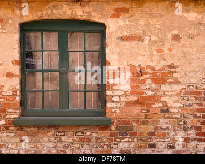 Old wooden window with green painted frame set in old red brick wall, Ticknall, Derbyshire, England, UK - Stock Photo