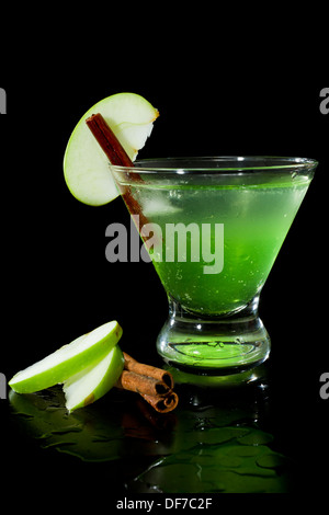 closeup of a green apple martini isolated on a black background garnished with an apple slice and a cinnamon stick - Stock Photo