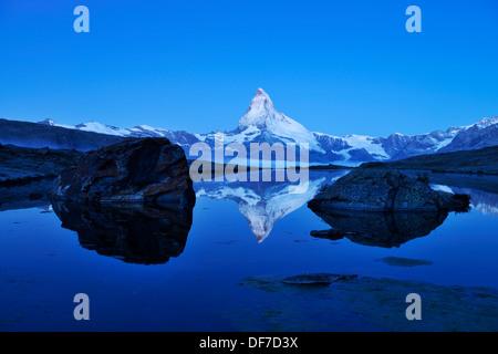 Mt Matterhorn reflected in Stellisee Lake at dusk, Zermatt, Canton of Valais, Switzerland - Stock Photo