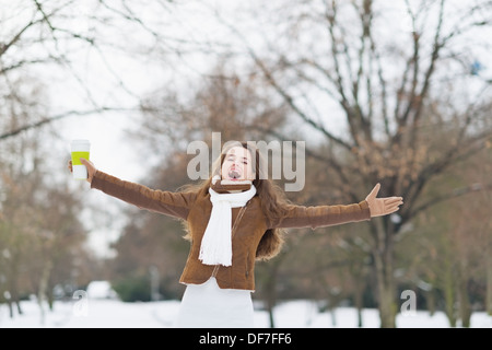Happy young woman with cup of hot beverage in winter outdoors rejoicing - Stock Photo