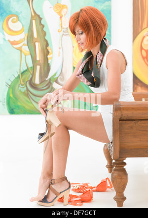 side view of young beautiful redhead woman sitting on a wooden bench changing her shoes, with colorful pictures - Stock Photo