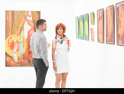 young beuatiful woman posing next to a caucasian man in an art gallery, holding colorful glasses of wine in their - Stock Photo