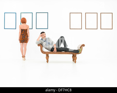 two young caucasian people in a white room with empty frames displayed on walls - Stock Photo