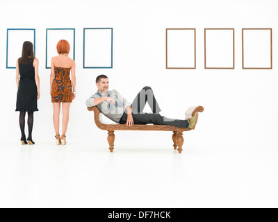 young caucasian man sitting in a relaxed position on a wooden bench, in a white room, with two women and empty frames - Stock Photo