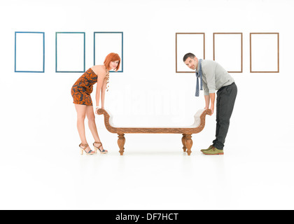 two caucasian people trying to lift up a wooden bench in a white room with empty frames displayed on walls - Stock Photo