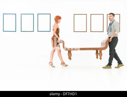two caucasian people carrying a wooden bench in a white room with empty frames displayed on walls - Stock Photo