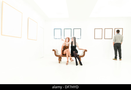 front view of two women sitting on a bench in a white room, pointing at some empty frames displayed on wall, with - Stock Photo