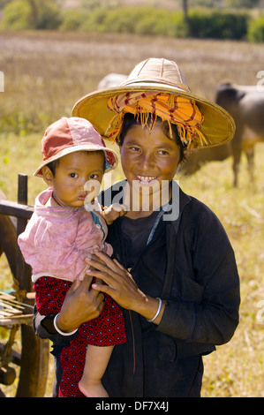 Pao tribe mother takes a break from thrashing wheat to hold her baby, Shan Plateau countryside, Shan State, Myanmar - Stock Photo