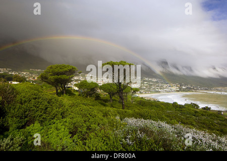A rainbow over Camp´s Bay near Cape Town, South Africa - Stock Photo