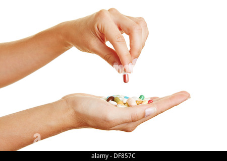 Female hand holding a red pill over different medicine in palm of hand - Stock Photo