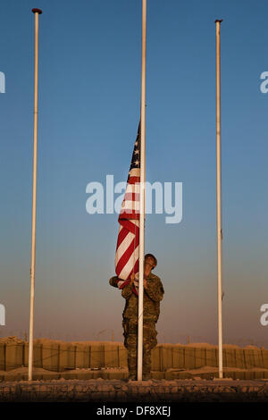 Tarin Kot, Afghanistan. 29th Sep, 2013. United States Army Spcs. Michael Arsenault lowers the flags of the Camp - Stock Photo