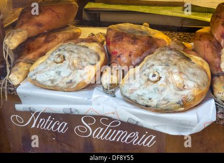 Whole parma hams in a traditional salumeria in the city centre, Reggio Emilia, Emilia Romagna, Italy - Stock Photo