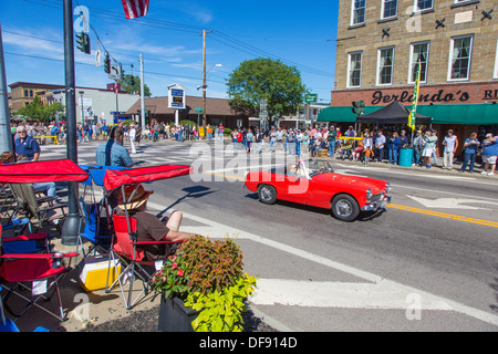 Vintage race cars driving though downtown Watkins Glen during the annual Vintage Race weekend Festival with spectators - Stock Photo