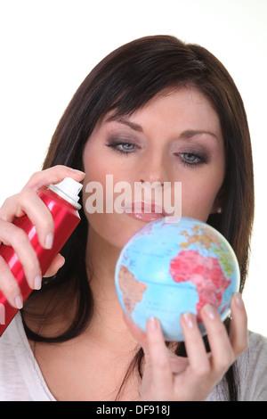 Woman spraying miniature globe - Stock Photo